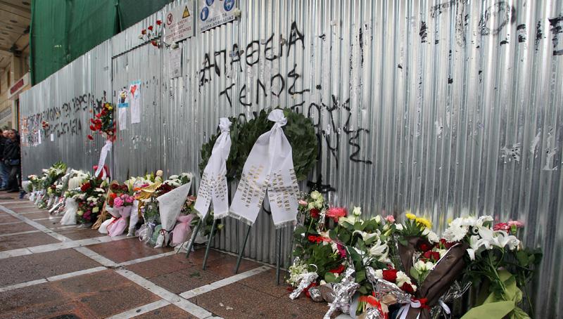 """Κόσμος έχει αφήσει λουλούδια στο υποκατάστημα της """"Μαρφίν"""" στην οδό Σταδίου όπου πριν από ένα χρόνο τρεις υπάλληλοι της βρήκαν τραγικό θάνατο λόγω ασφυξίας από μολότοφ που έριξαν νεαροί στην τράπεζα, Πέμπτη 5 Μαΐου 2011."""