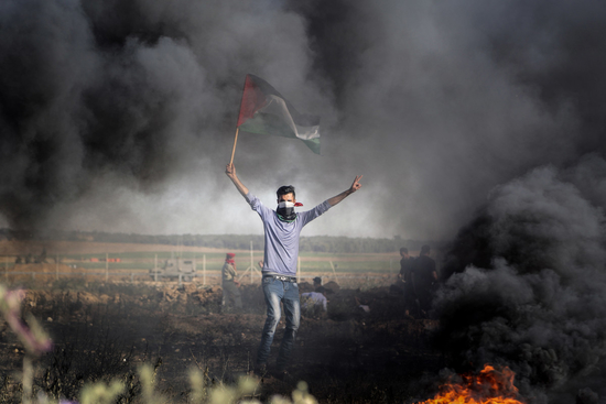 A Palestinian protester waves the national during clashes with Israeli security forces following a protest near the border fence east of Jabalia refugee camp, against the blockade